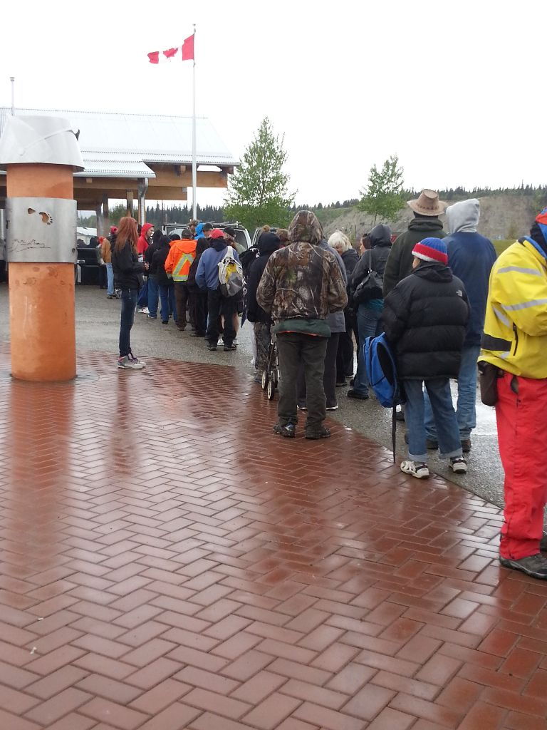 People waiting in the rain for hamburgers, hotdogs, chips, corn on the cob, and juice or coffee
