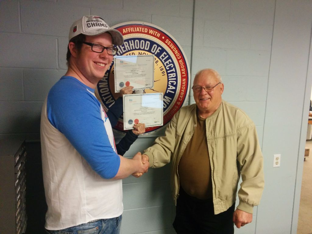 Brandon Rigdon receiving his red seal from IBEW 993 President, Ron Bourdois